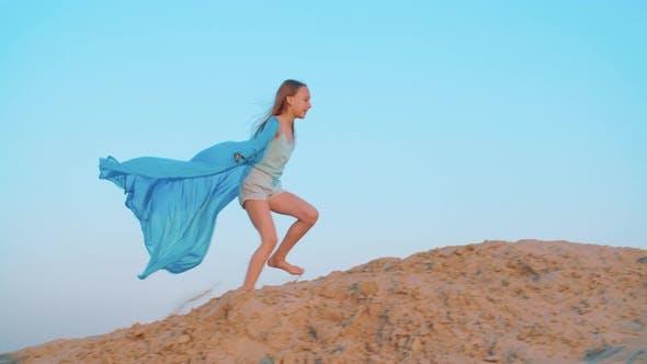 Thumbnail for Verspieltes Mädchen Teenager in Blue Pareo Walking auf Sandy Hill in Summer Desert. Fröhliches Mädchen in Blau