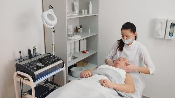 Beautician Massages the Face of an Older Woman