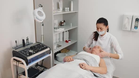 Kosmetikerin massiert das Gesicht einer älteren Frau