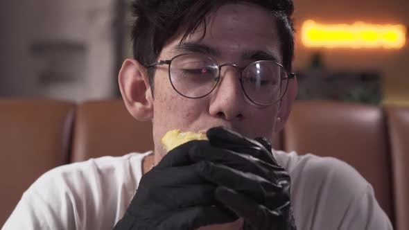 Cover Image for Portrait of Cute Skinny Young Man in Glasses and Black Gloves Eating Tasty Shawarma