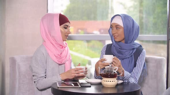Thumbnail for Two Young Beautiful Muslim Business Women in Hijab Drinking Tea in Cafe