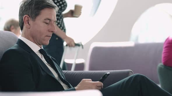 Business man waiting in airport lounge on mobile phone