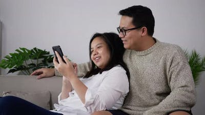 Happy couple using smartphone play mobile game