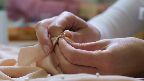 Thumbnail for Female Hands Cutting Buttons Before Dry Cleaning