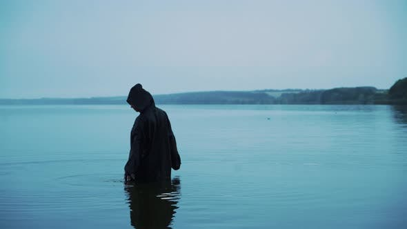Evil witch in black cloak with hood in the river