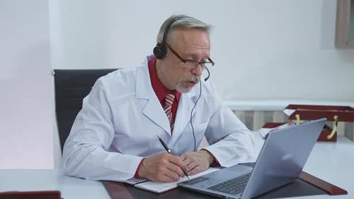 Doctor wear headset who is listening to patient and then talking about his symptom online.