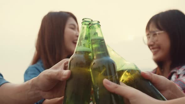 Group of Asia friends focus on couple girls cheers toast of bottle beer enjoy party with happy.