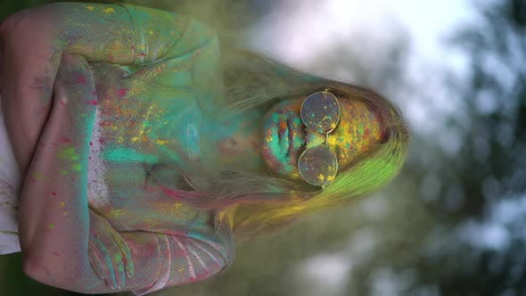 Thumbnail for Vertical Video, Portrait of Woman Standing Being Covered in Coloured Powder at Holi Festival