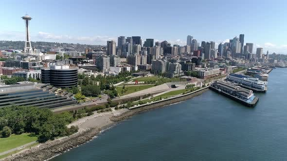Cover Image for Helicopter View Of Downtown Seattle Buildings In Skyline And Waterfront Piers On Sunny Summer Day