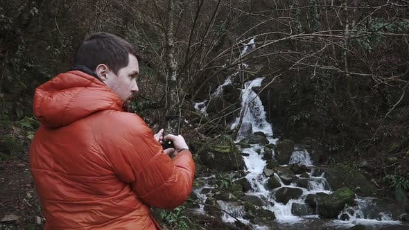 Adventurer with Smartphone in a Forest
