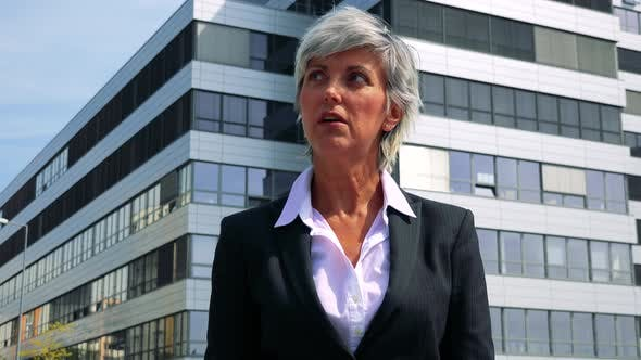 Thumbnail for Unhappy Business Middle Age Woman Is Angry - Company Building in the Background