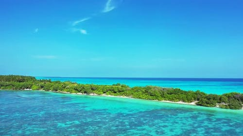 Luxury aerial travel shot of a sunshine white sandy paradise beach and aqua blue water background in