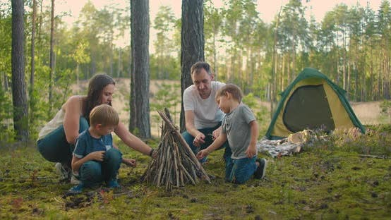 Thumbnail for Family Sits Around a Campfire on a Summer Evening. Children with Their Parents Are Resting in the