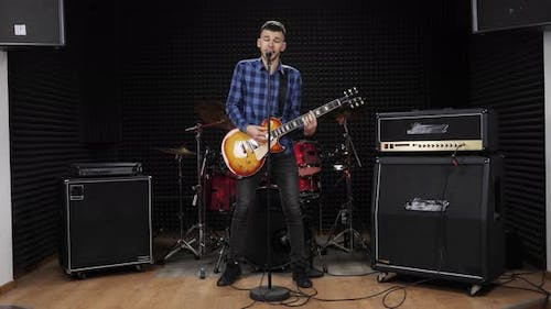 Guitarist singer in rehearsal studio is singing rock songs to microphone at recording vocal studio