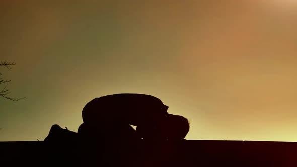 Religious Man Bows on Sunset