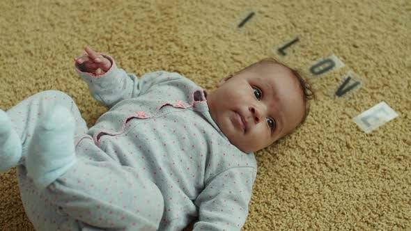 Thumbnail for Adorable Infant Girl Lying on Carpet