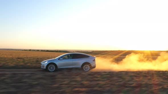 Aerial Shot of Electrical Car Speeding Through Dusty Route. Ecology Friendly Auto on Electric Charge