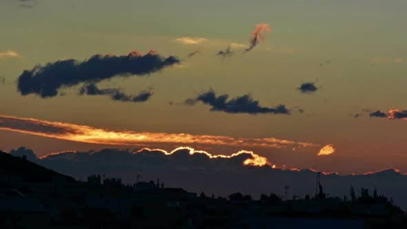 Thumbnail for Time lapse of dawn. Sun rising up between clouds with a cityscape