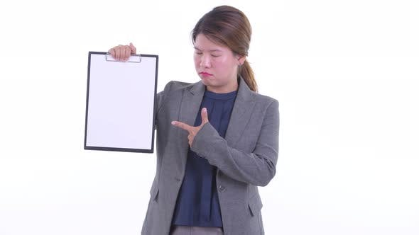 Thumbnail for Stressed Young Asian Businesswoman Showing Clipboard and Giving Thumbs Down