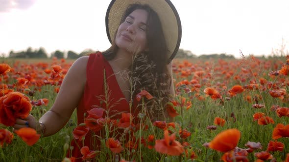 Beautiful Happy Young Woman in a Poppy Field
