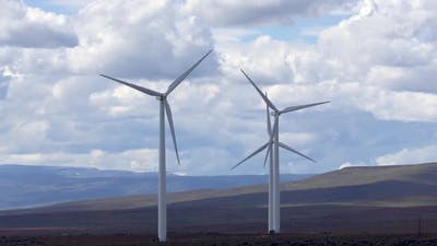 Wind mills spinning across grassy plains