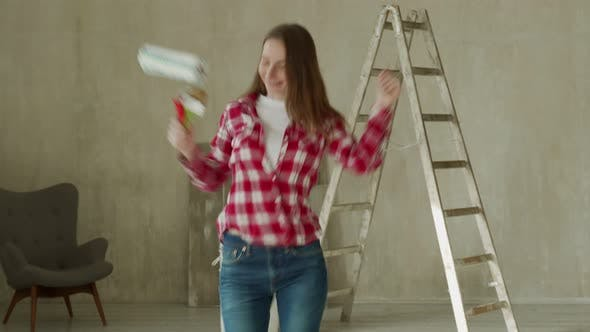 Dancing Woman Painting the Wall with Paint Roller