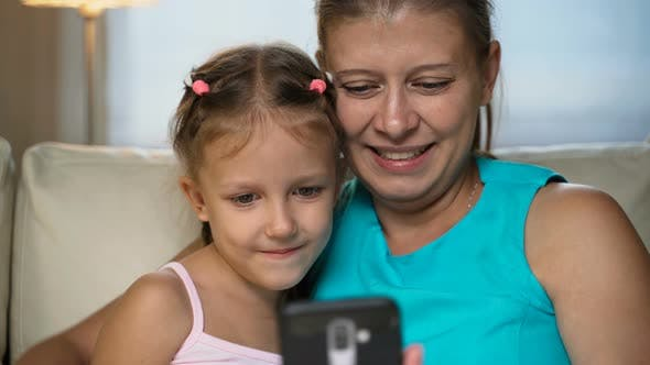 Thumbnail for Little Girl Child With Mother Home On Sofa Using Smartphone