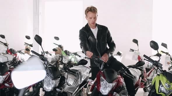 Thumbnail for Young Man Choosing Motorbike at a Shop