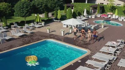 Aerial Shot of Multiracial Friends Jumping in Pool