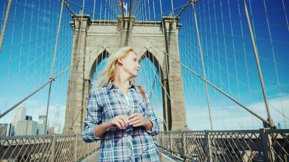 Cover Image for Woman Tourist Leisurely Walking Along the Brooklyn Bridge in New York. USA Travel