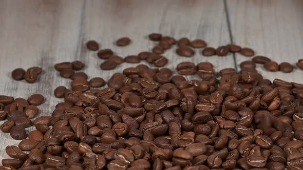 Thumbnail for Roasted coffee beans falling on wooden table