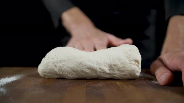 Thumbnail for Cook Rolls Out Dough on a Wooden Table in a Dark Kitchen