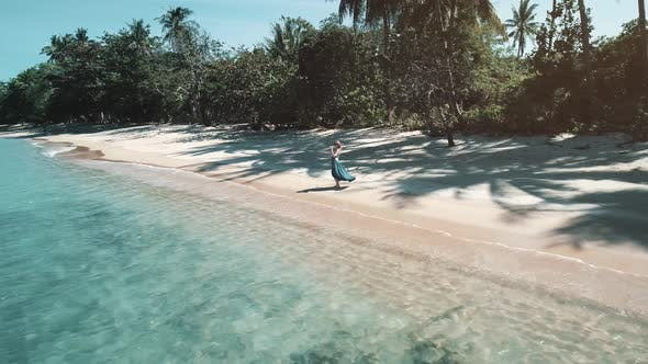 Aerial of Beautiful Woman in a Long Blue Dress Standing Barefoot on Paradise Beach Sand Near Sea