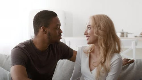 Loving Diverse Couple Talking Sitting On Sofa At Home
