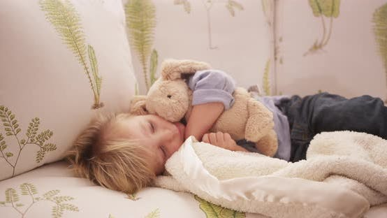 Thumbnail for Closeup of an adorable sleepy young child lying on a sofa