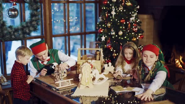 Thumbnail for Two Elves are Sitting at the Table with a Little Boy and Girl and Show them Christmas Gifts
