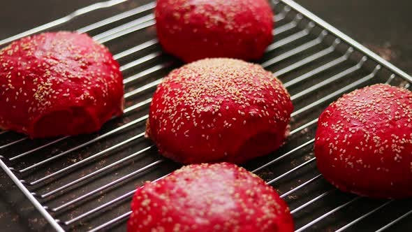 Fresh Baked Red Homemade Burger Buns with Sesame Top View. Placed on Metal Grill.
