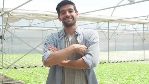 Junger hispanischer Geschäftsmann mit Blick in die Kamera auf Bio-Farmbetrieb mit Qualitätsstandard.