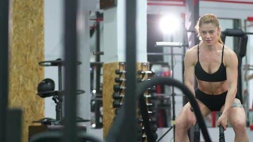 Sportlerin trainiert im Functional Training Gym trainiert mit Battle Ropes