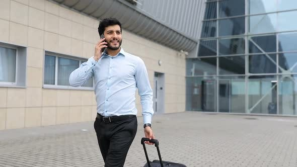 Business Trip. Handsome Man With Phone And Suitcase At Airport