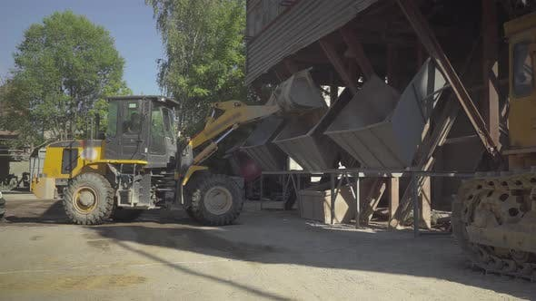 Thumbnail for Wide Shot of Tractor Unloading Bulk Material on Production Site on Sunny Day. Machinery Working on