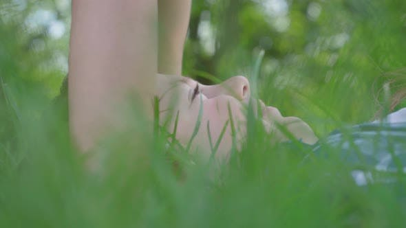 Cover Image for Close Up Portrait of Little Girl Kissing Forehead of the Boy Lying in the Grass. A Couple of Happy