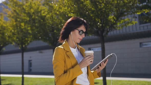 Thumbnail for Attractive young businesswoman in sunglasses is drinking coffee
