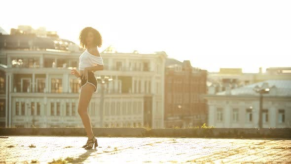 Thumbnail for A Young Woman in Small Shorts Performing Attractive Sexy Dancing on the Roof - Playing Her Hips -