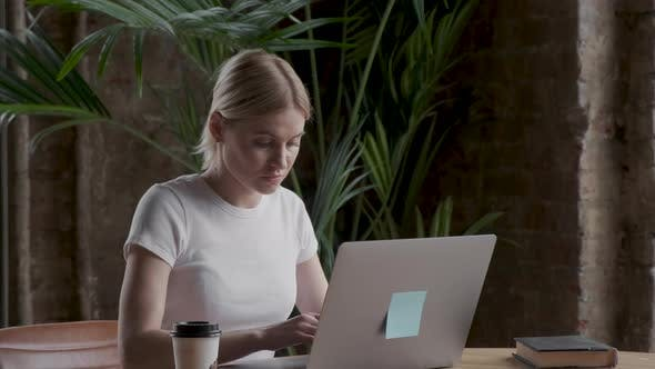 Female employee looking at laptop in home workplace. Attractive young female freelancer
