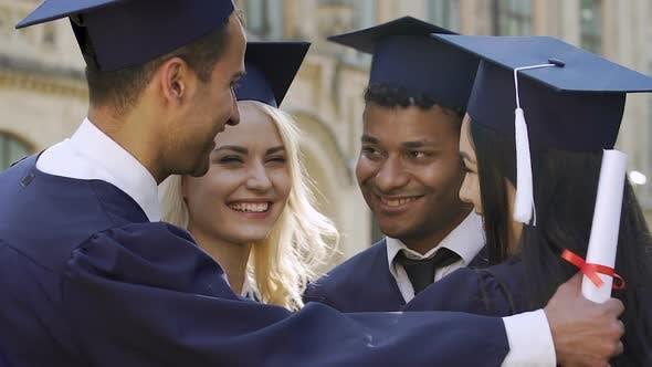 Thumbnail for Smiling graduation students embracing, congratulations on receiving diplomas