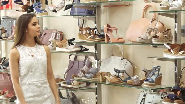 Woman Takes High Heel Sandals From the Rack at the Shoe Shop