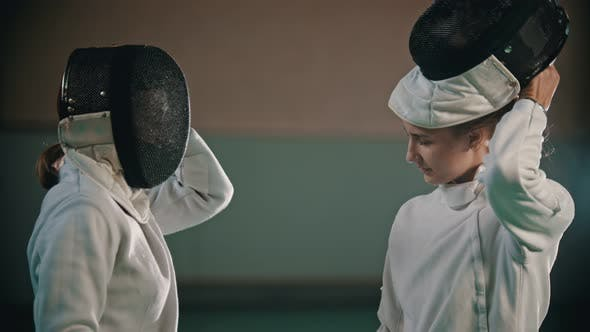 Thumbnail for Two Young Women Fencers Putting on Their Helmets and Going on the Training