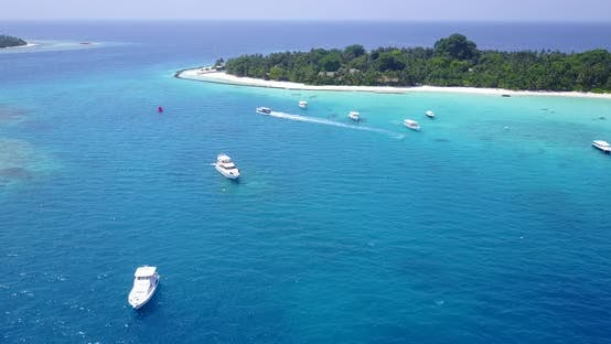Daytime aerial tourism shot of a paradise sunny white sand beach and blue water background in 4K