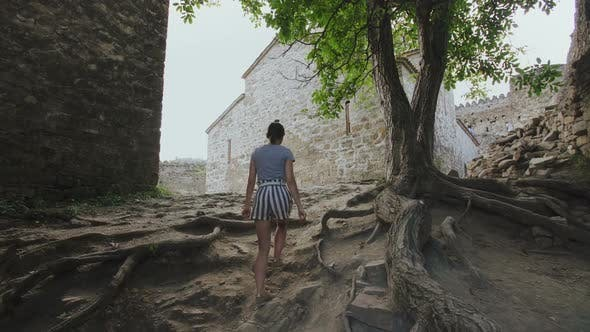 Thumbnail for Girl Walks Path in Territory of Ancient Defensive Fortress Around a Church in Highlands Georgia